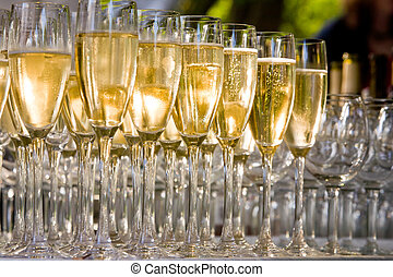 glasses of champagne - a row of glasses filled with...