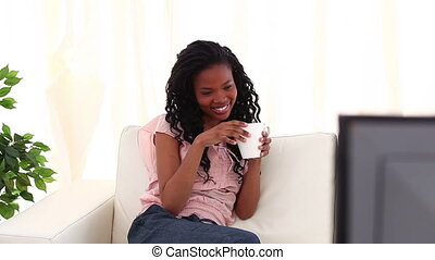 Brunette woman drinking a cup of coffee in her living room