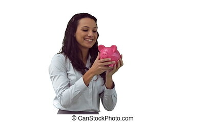 Brunette in slow motion kissing a piggy bank against a white...