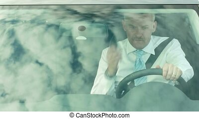 Businessman driving car with phone