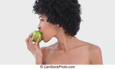 Woman eating a green apple against white background