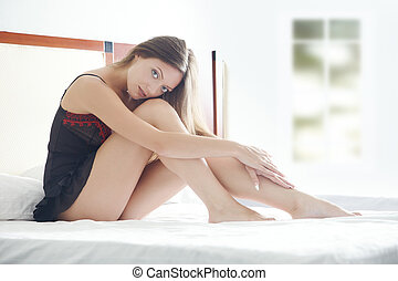 Morning - Young lady at home sits on the bed at early...