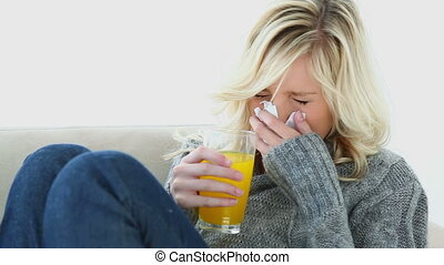Sick woman drinking orange juice on a couch