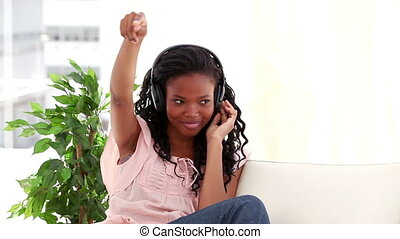 Happy brunette woman listening to music in her living room