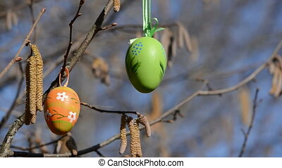 two easter eggs on nutwood branches and wind
