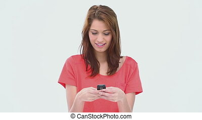 Brunette haired woman writing a text message against a white...