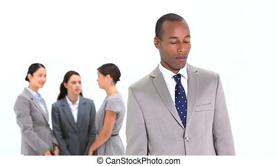 Smiling businessman standing in front of colleagues against...