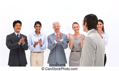Man being congratulated by his co-workers against a white...