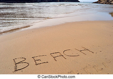 The word beach written in the sand