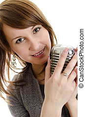 Young woman holding a retro-microphone. Isolated on white.