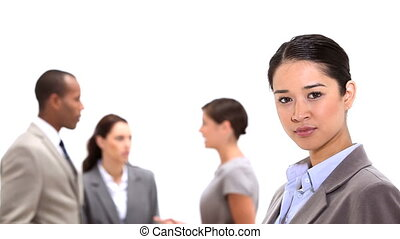 Businesswoman standing with co-workers behind her against a...
