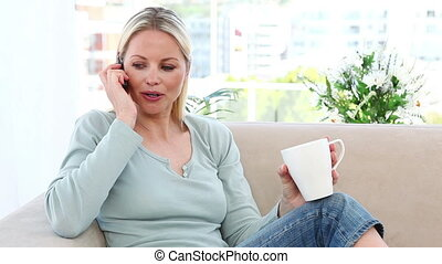 Woman on the phone holding a mug in a living room