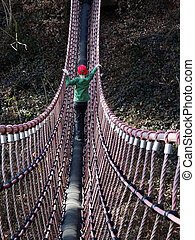Boy on swing bridge - A boy walks on a swing bridge