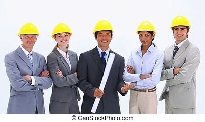Business team wearing hardhats standing side by side -...