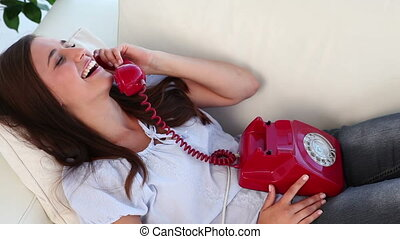 Brunette woman using her red phone in her living room