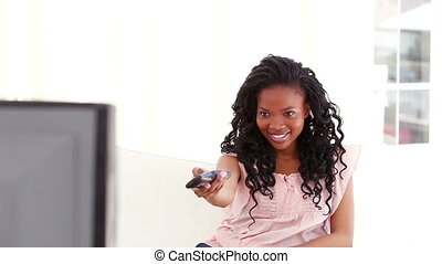 Smiling woman changing her tv station in her living room