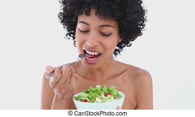 Black haired woman eating salad against white background