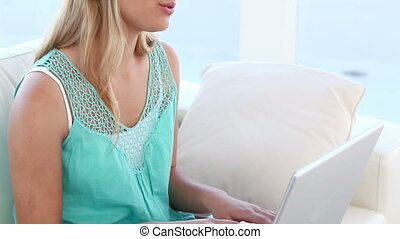 Blonde woman listening to music in front of her laptop