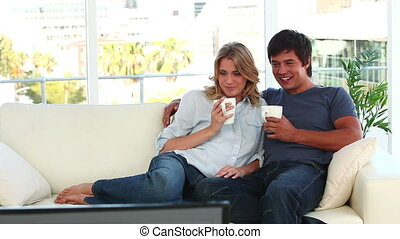 Happy couple watching the television together in their...