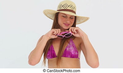 Woman in a bikini holding pink sunglasses
