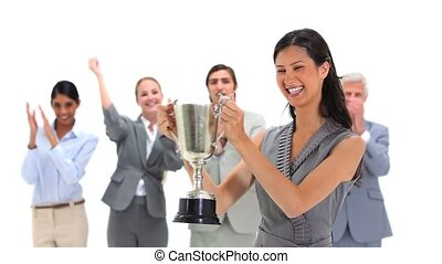 Woman holding a trophy with co-workers applauding against a...