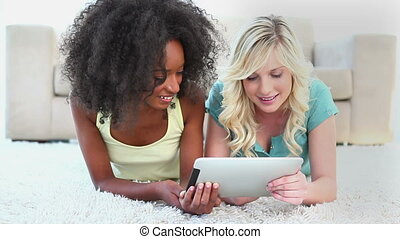 Friends using an ebook on a carpet in a living room