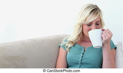 Blonde haired woman drinking coffee