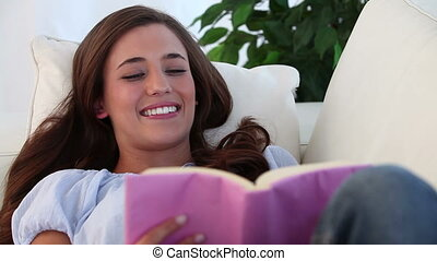Smiling woman reading a novel in the living room