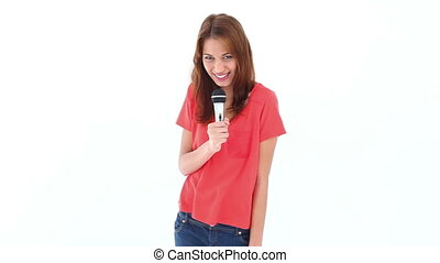 Brunette haired woman singing with a microphone against...