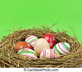Easter eggs in nest on green background