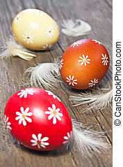 Three painted easter eggs on wooden table