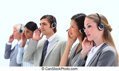 People in suits speaking into headset against a white...