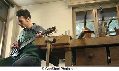 Man at work as artisan with guitar - Adult Italian man at...
