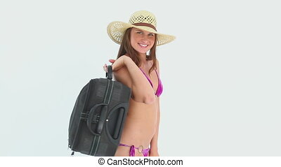 Woman in bikini holding a suitcase against white background