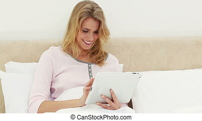 Smiling blonde woman using an ebook in her bedroom