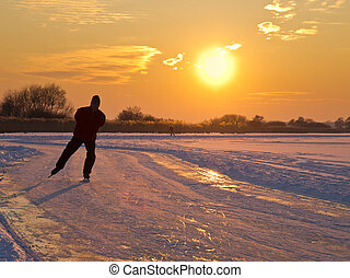 An ice skater is aproaching during sunset