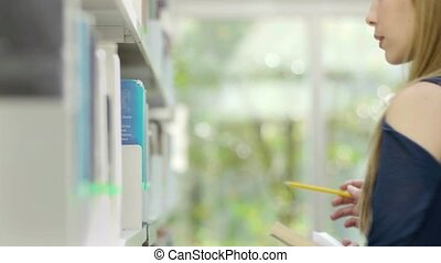 Woman choosing book on shelf - Female blonde college student...