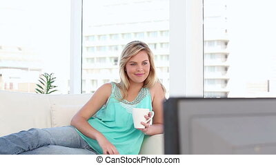 Cheerful blonde woman watching the television