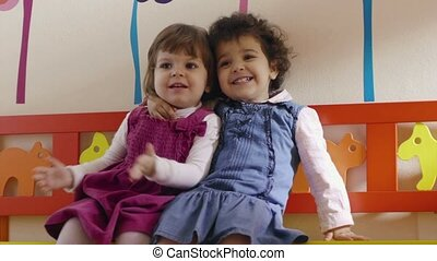 Baby girls playing and smiling - Kindergarten, two cute baby...
