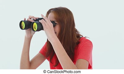 Laughing brunette haired looking through binoculars against...