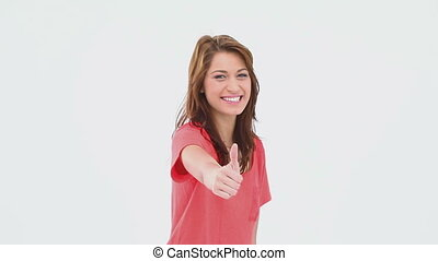 Brunette haired woman the thumb-up against white background