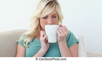 Woman drinking from a mug in a sofa