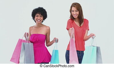 Two women dancing with shopping bags against white...