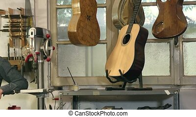artisan at work in guitar shop - Portrait of Italian adult...