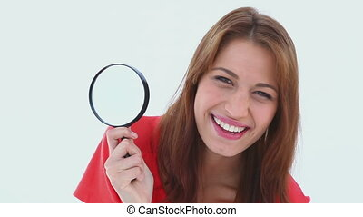 Brunette haired woman holding a magnifying glass against...