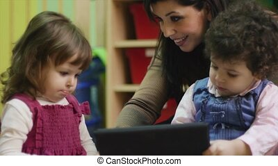 School teacher with children and pc