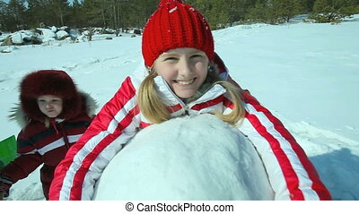 Kids and snow - Smiling girl in winterwear hugging a huge...