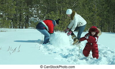 Winter weekend - Parents making a snowman on a sunny winter...