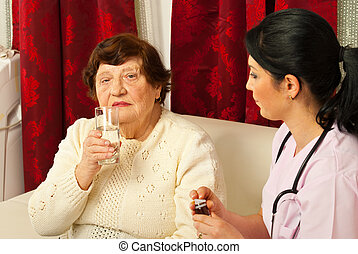 Nurse giving pills and water to senior