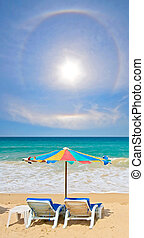 Couple chair and multi-color umbrella on the beach with...